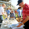 City of Enid Mayor Bill Shewey glances through one of the new 4RKids calendars Saturday as Rep. Mike Jackson and John Enns prepare for the annual awards ceremony at David Allen Memorial Ballpark's home plate. (Staff Photo by BONNIE VCULEK)