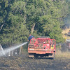 Grass rigs from Enid, Waukomis and Drummond work on a grass fire that was blown into a thicket of trees along Leona Mitchell Blvd. Tuesday. (Staff Photo by BILLY HEFTON)
