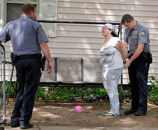 Enid police officers handcuff a suspect in a stabbing incident Monday on east Cherokee. (Staff Photo by BILLY HEFTON)