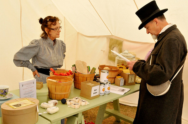 Tom Morphew reads over a list of items being sold by Lori Carroll in the general store Saturday during the Frontier Festival at the Cherokee Strip Heritage Center. (Staff Photo by BILLY HEFTON)