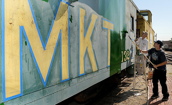 Sam Morgan and Bill Smart were among the volunteers Saturday who painted railcars at the Railroad Museum of Oklahoma. (Staff Photo by BILLY HEFTON)