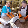 Tammy Grimes and Brenda Gripr prepare hamburger meat for the elementary schools Thursday at the Enid Public Schools central kitchen. (Staff Photo by BILLY HEFTON)