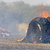 A hay bale burns as a grass rig works on a grass fire along Leona Mitchell Blvd. Tuesday. (Staff Photo by BILLY HEFTON)