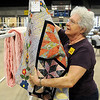 Eleanor Smith hangs a quilt for judging Thursday at the Garfield County Fair. (Staff Photo by BILLY HEFTON)