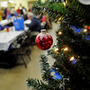 Christmas decorations hang from the tree at Our Daily Bread Tuesday during Christmas dinner. (Staff Photo by BILLY HEFTON)