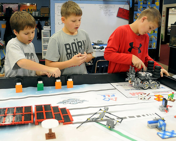 Bryce Morris, Krese Smith (from left) explain how their robot works as Nate Edwards (right) begins the robot's next programmed task Friday in Roy Bartnick's classroom at Chisholm Elementary School. The team finished 2nd in programming during the Senior Solutions 2012-2013 Oklahoma FLL Championship Tournament, sponsored by The Chickasaw Nation and Oklahoma State University. (Staff Photo by BONNIE VCULEK)
