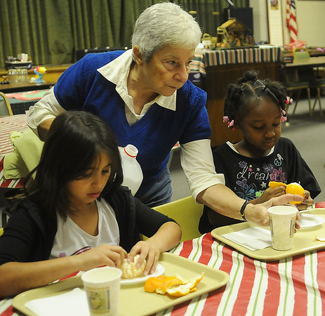 Dottie Harkin (center) pours milk for Ruby de Alba and Auvianna Dority as the children enjoy an after school snack during Super Kids Tutoring Wednesday at University Place Christian Church. (Staff Photo by BONNIE VCULEK)