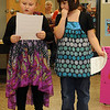 Isabella Brown and Samantha Payne (from left) welcome guests to the Prairie View Elementary School first grade class book signing Thursday. (Staff Photo by BONNIE VCULEK)