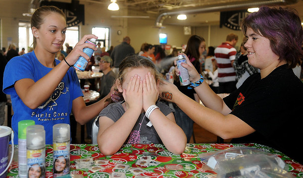 Jordan Smith covers her nose as Hope Yerian (left) and Amanda Metcalf (right) apply color to Smith's hair Saturday during March of Dimes Breakfast with Santa at the Enid High School food court. (Staff Photo by BONNIE VCULEK)
