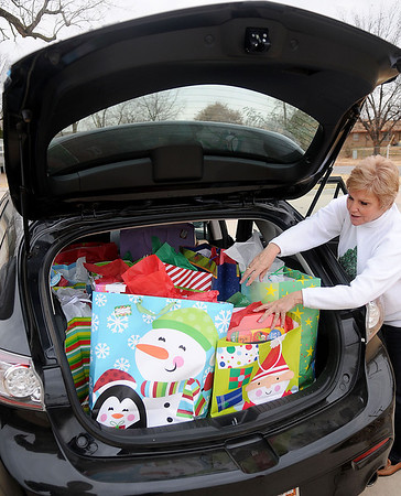 Sharon Robinett-Morris places Christmas gifts into the back of a car at the Thelma J,. Gungoll Youth and Family Center Wednesday. The presents will be delivered to more than 160 school-age children in 10 different schools across Garfield County as part of Project Santa. (Staff Photo by BONNIE VCULEK)