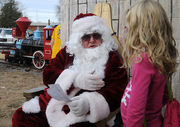 Santa holds Emma Kate and Elliott Kruska's Christmas wish list as he shares Kiwanis train rides with area children Saturday at Meadowlake Park North. (Staff Photo by BONNIE VCULEK)