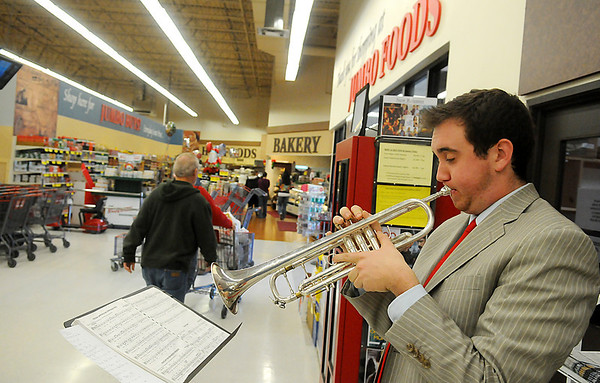Kegan Tuohy entertains shoppers at the westside Jumbo's with Christmas carols played on his trumpet. (Staff Photo by BILLY HEFTON)