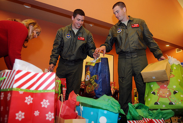 """Vance Air Force Base pilots Chris Hall (center) and Mike Riggs (right) load more than 160 gifts for children into waiting cars at the Thelma J. Gungoll Youth and Family Center Wednesday. Shelby Hall, director of development at the center, organizes the """"Project Santa"""" event with the help of therapists, counselors and volunteers. (Staff Photo by BONNIE VCULEK)"""