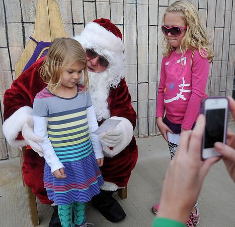 Elliiott and Emma Kate Kruska present Santa with a Christmas wish list Saturday during the Kiwanis Santa Train rides at Meadowlake Park North. (Staff Photo by BONNIE VCULEK)