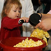 Riley Caruthers fills a glove with popcorn Saturday as she enjoys the March of Dimes Breakfast with Santa festivities at Enid High School. (Staff Photo by BONNIE VCULEK)