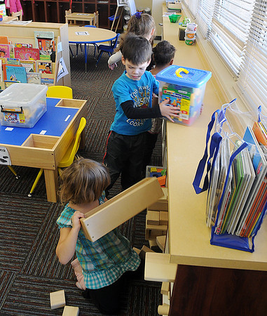 Pre-k students at Monroe Elementary help to organize their remodeled classroom. (Staff Photo by BILLY HEFTON)