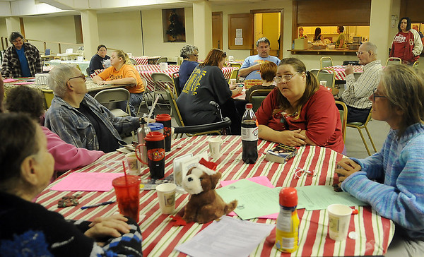 As volunteers prepare the Mamre meal (top, right), guests relax in the warm surroundings at University Place Christian Church Monday. The church serves as many as 100 meals during the weekly event. (Staff Photo by BONNIE VCULEK)