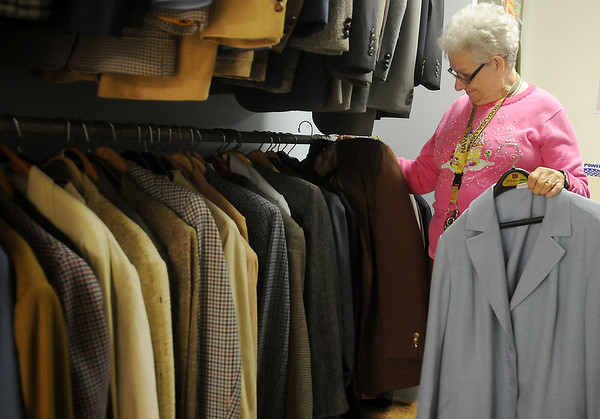 Linda Bair arranges men's suit coats in the Second Mile Clothing Closet at University Place Christian Church Monday evening. Bair and her husband, A. J., spend several hours a week organizing the donated items, which are free to those in need. (Staff Photo by BONNIE VCULEK)