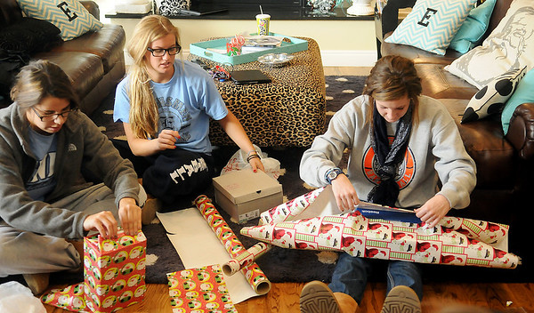 The Enid High School Pacers basketball team members wrap Christmas gifts for their adopted family Friday at 1205 York. New bicycles, toys and clothing will be delivered to two young boys and their older sister Saturday morning. (Staff Photo by BONNIE VCULEK)