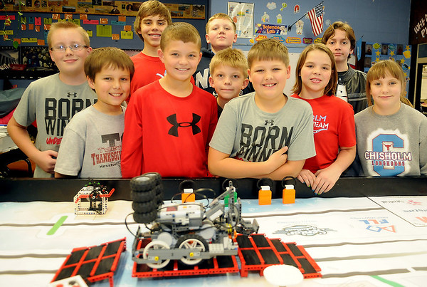 Chisholm Robotics Team members pause for a portrait next to their Senior Solutions competition board Friday. The students, under the direction of instructor Roy Bartnick, placed second in programming during the 2012-2013 Oklahoma FLL Championship Tournament. (Staff Photo by BONNIE VCULEK)