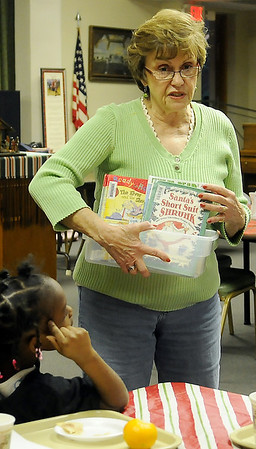 Annie Galbreath tells Adams Elementary School students about several of the holiday stories that they will read together during Super Kids activities at University Place Christian Church Wednesday. (Staff Photo by BONNIE VCULEK)