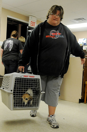 Tennille Chesnut, from Enid, carries one of the 30 rescued dogs into the Enid SPCA for evaluation and treatment Saturday night. Vickie Grantz, executive director for the Enid SPCA, assisted Dr. Kristy Krueger, DVM, with the animal assessments. Twenty of the dogs seized by the Harper County Sheriff Department were transported to Enid for care. (Staff Photo by BONNIE VCULEK)