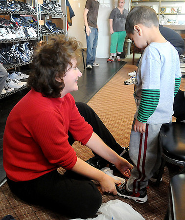 Juanita Gates finds a pair of shoes for Georgo Quintana Saturday during IOOF hall. (Staff Photo by BILLY HEFTON)