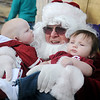 Santa chuckles as little Jason Whisenhunt (left) glances toward him during a photo with sleepy Aythen Kausek Saturday during rides on the Kiwanis Santa Train at Meadowlake Park North. (Staff Photo by BONNIE VCULEK)