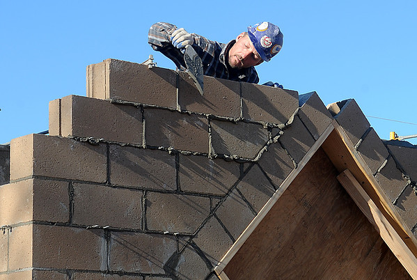 Bobby Midas of Allen Masonry works on the building for the Kiwanis Club carousel Monday at Meadowlake Park. (Staff Photo by BILLY HEFTON)