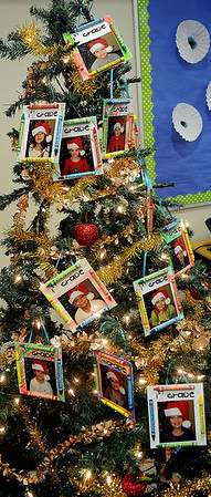 Specially designed Christmas ornaments adorn a first-grade tree at Prairie View Elementary School Thursday. The students created their unique cards with individual photographs, fun crayons and craft glue sticks. (Staff Photo by BONNIE VCULEK)