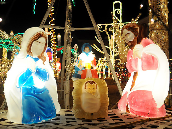 Exterior Christmas lighting at a North Enid home features the Christ child with Mary and Joseph throughout the holiday season. (Staff Photo by BONNIE VCULEK)