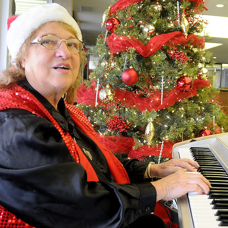 Sandy Ewing Luginbill entertains Security National Bank guests during the annual holiday open house Wednesday. (Staff Photo by BONNIE VCULEK)