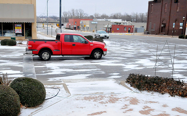 Traffic moves along on the snow spotted street of downtown Tuesday. (Staff Photo by BILLY HEFTON)