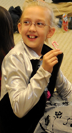 Adry Chattam enjoys a candy cane during Central National Bank's holiday open house Friday. (Staff Photo by BONNIE VCULEK)