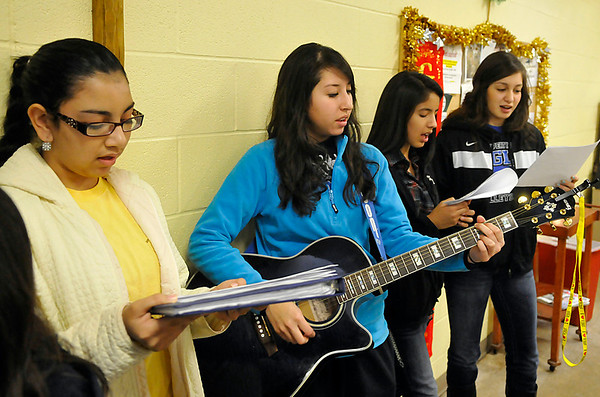 (Left to right) Viviana Rojas, Karina Orozco, Arely Tarango and Jauette Armenta from the Cristo Rey Baptist Church in Hennessey perform Chrsitmas carols at Our Daily Bread Tuesday during Christmas dinner. (Staff Photo by BILLY HEFTON)