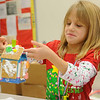 Kassydi Reisner admires her gingerbread house decorations during the March of Dimes Breakfast with Santa Saturday at Enid High School. (Staff Photo by BONNIE VCULEK)