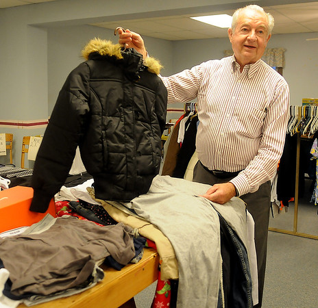 Jerry Galbreath holds up one of the many new clothing items that will be available for individuals in need at Christmas during an interview Monday at University Place Christian Church. (Staff Photo by BONNIE VCULEK)