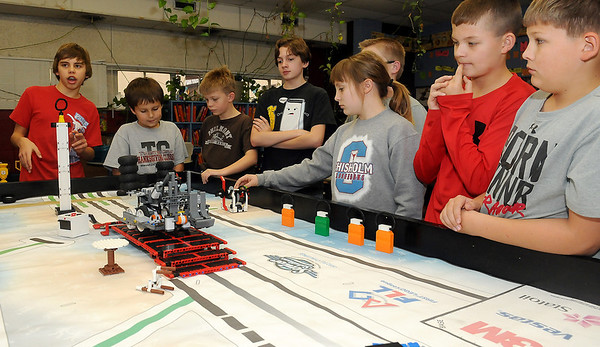 Brent Tilley (far left), one of the co-captains for the Chisholm Robotics Team, explains the building and programming of the competition robot for the Senior Solutions 2012-2013 Oklahoma FLL Championship Tournament. Chisholm finished second in the competition. (Staff Photo by BONNIE VCULEK)