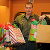 Mike Riggs, a Vance Air Force Base pilot, carries Christmas gifts to waiting vehicles at the Thelma J. Gungoll Youth and Family Center Wednesday. More than 160 children in 10 different schools across Garfield County will receive presents through Project Santa this year. (Staff Photo by BONNIE VCULEK)