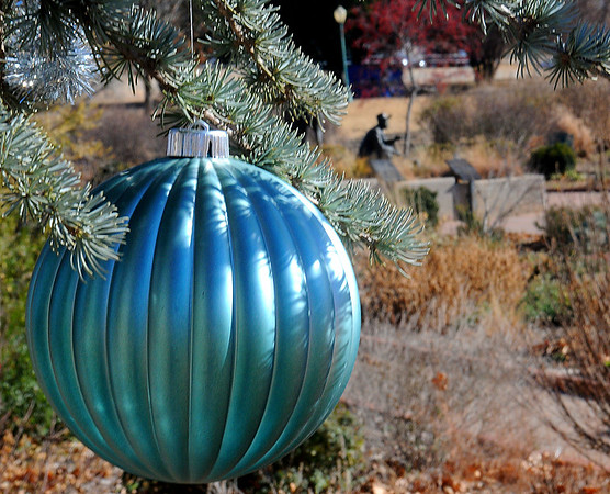 Christmas decorations hang from a pine tree at Dillingham Garden Tuesday. (Staff Photo by BILLY HEFTON)