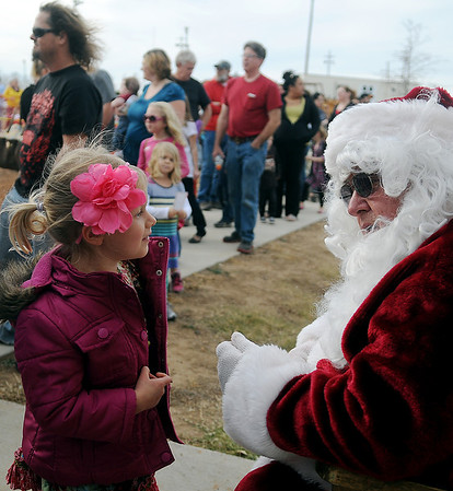 Mia Meier visits with Santa as children and their parents wait in a long line for a few words with Jolly Ol' St. Nick and a Kiwanis Train ride Saturday at Meadowlake Park North. (Staff Photo by BONNIE VCULEK)