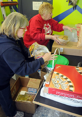 Sheri Wetekam and Juanita Barker pack boxes with cookies to be taken to the military welcome center in Oklahoma City. (Staff Photo by BILLY HEFTON)