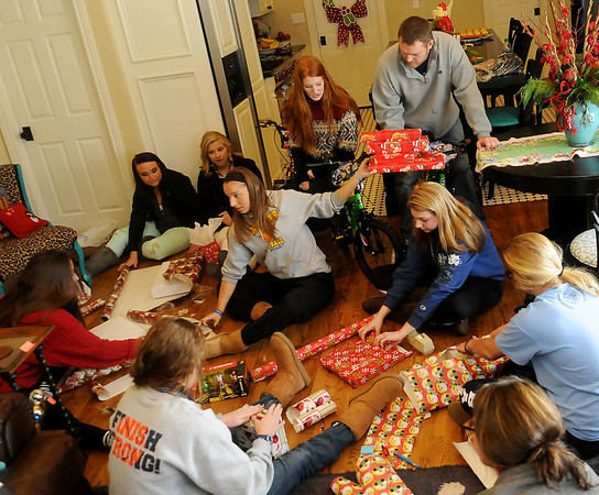Enid High School Pacers basketball team and their head coach, Robb Mills wrap Christmas gifts for their adopted family Friday at 1205 York. New bicycles, toys and clothing will be delivered to two young boys and their older sister Saturday morning. (Staff Photo by BONNIE VCULEK)