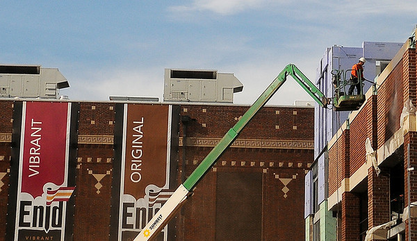 Giant banners hang on the east side of Convention Hall as a construction worker (top, right) power washes the exterior brick on the new Enid Event Center Friday. The center is slated to open next year. (Staff Photo by BONNIE VCULEK)