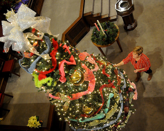 Carol Broughton, the financial manager for First Presbyterian Church, admires the hand-crocheted scarves on a large Christmas tree inside the church sanctuary Thursday. All of the scarves will be presented to children in the tutoring program and individuals who attend Saturday Mana. (Staff Photo by BONNIE VCULEK)