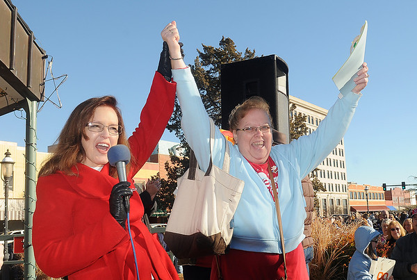April Danahy (left) hold up the arm of Glaida Nixon, the grand prize winner in the 9th annual Candy Cane Cash Giveaway Saturday on the Garfield County Courthouse lawn. (Staff Photo by BILLY HEFTON)