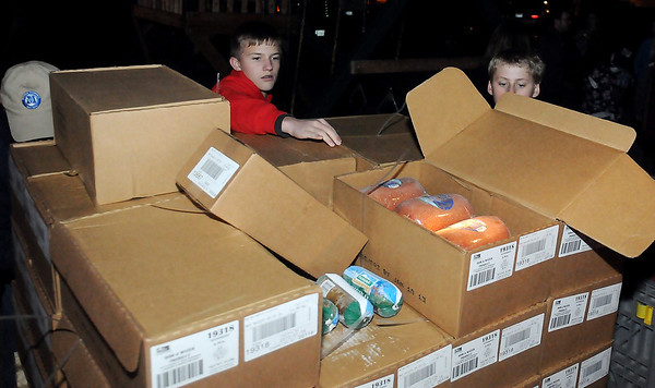 Volunteers open boxes of sausage, ham and chicken donated by Mustang Fuel Corporation employees Tuesday as they prepare for the Regional Food Bank distribution of food to 160 hungry families at Loaves and Fishes, 701 E. Maine. (Staff Photo by BONNIE VCULEK)
