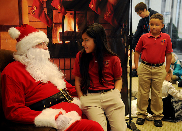 Nadia Rodriguez (center) shares a secret with Santa as Jadyn Ward (right) waits for a chance to visit with the Jolly St. Nick Friday during Central National Bank's Holiday open House. (Staff Photo by BONNIE VCULEK)