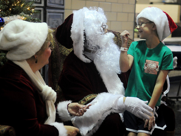 Travis Moore jokes with Santa and Mrs. Claus during the March of Dimes Breakfast with Santa Saturday at Enid High School cafeteria. (Staff Photo by BONNIE VCULEK)