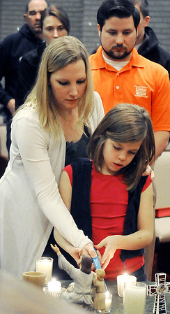 Tiffany Harvey helps her daughter, Jersey, light a candle during a vigil at Central Christian Church for the victims in the Newtown, CT school shooting. (Staff Photo by BILLY HEFTON)